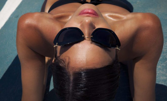 Luxury by the pool, beautiful woman sunbathing