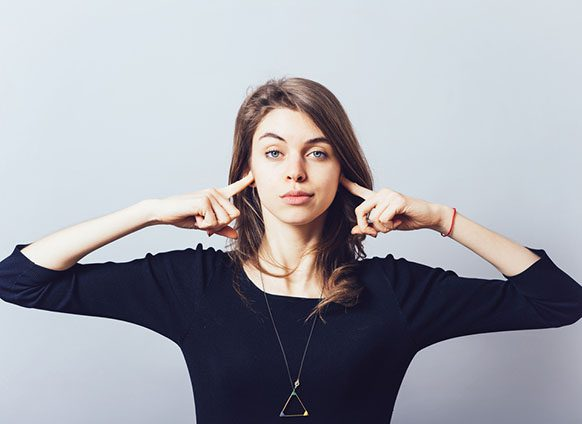 Woman in blue shirt with fingers in her hears. Twelve Ways Successful People Handle Toxic People