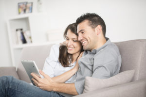 Young couple sitting on the couch sharing their tablet.