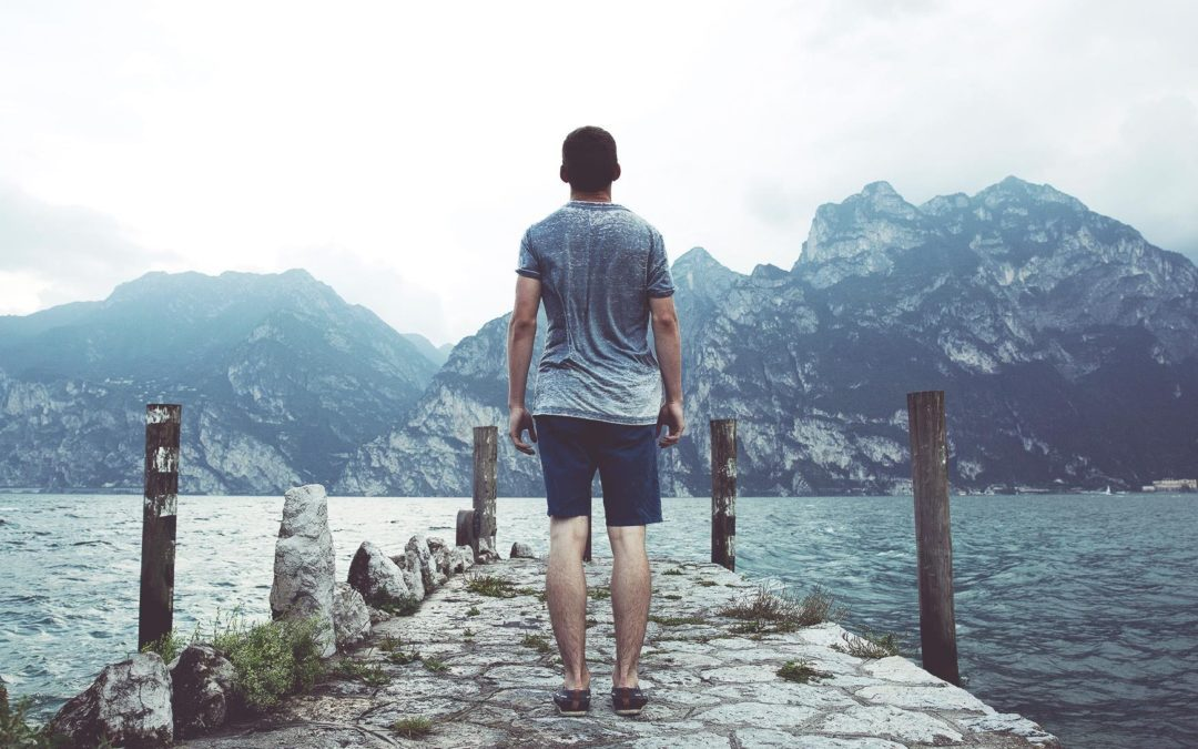 man standing on shore looking at water