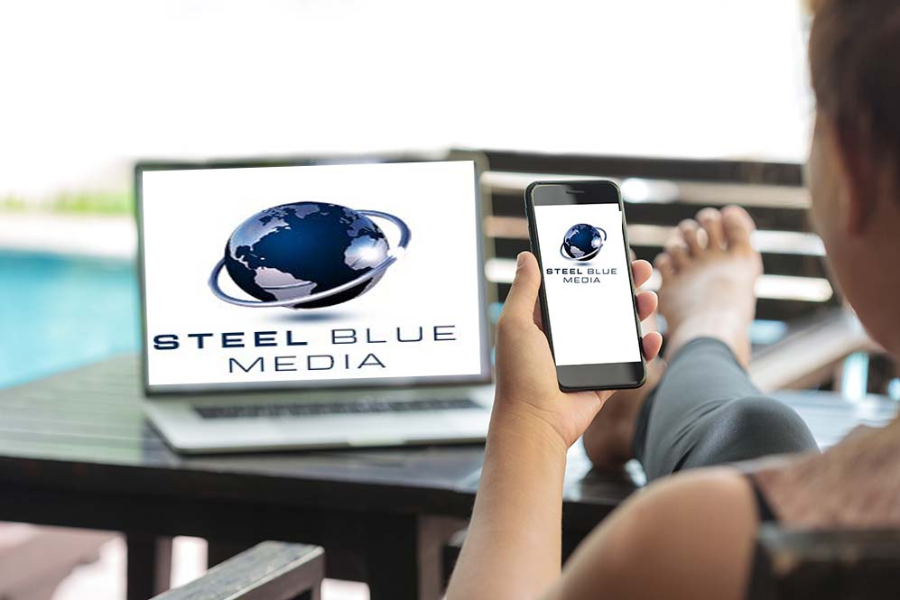 Woman holding cell phone with Steel Blue Media logo on it