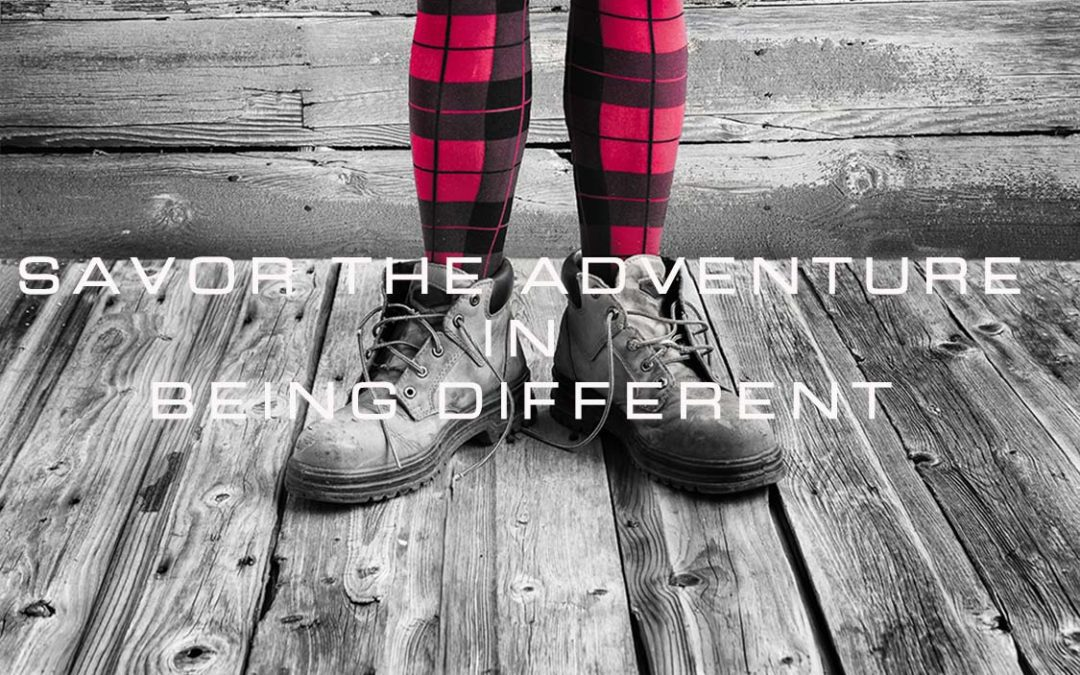"Black and white backgound, women's legs in red and black plaid, ""discover the adventure in being different""."